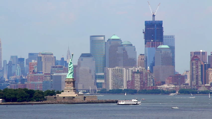 The Statue of Liberty near Ellis Island with New York City in the background.