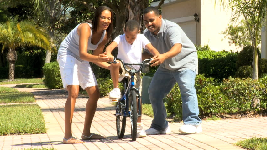 Cute young african american boy being encouraged by his parents as he practices riding his bicycle - HD stock footage clip