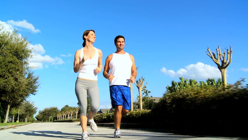 Young couple keeping fit jogging on suburban road