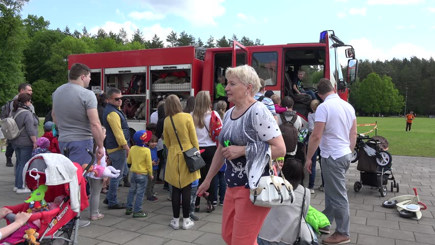 VILNIUS, LITHUANIA - MAY 31,2015: Unidentified parents with kids around military emergencies fireman truck during show on May 31, 2015 in Vilnius, Lithuania. Static shot. 4K