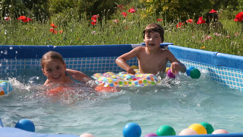 Mother with baby and little girl splashing the water of for Baby garden pool