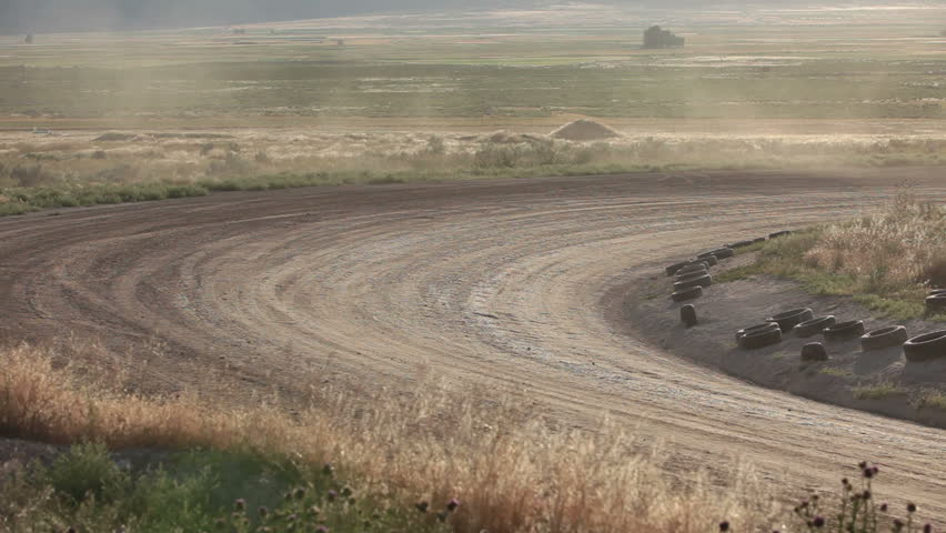 Race cars speeding fast on dirt oval course. Highly modified stock cars driving and racing on a very dirty and dusty track corner. High speed around dusty corner. - HD stock footage clip