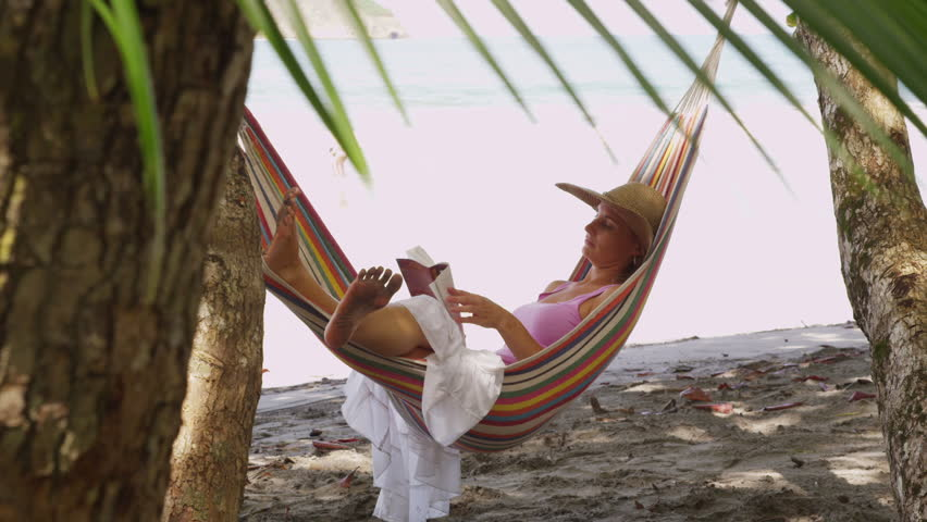 Cinemagraph - Woman sitting in hammock reading book, Costa Rica. Looping Motion Photo.