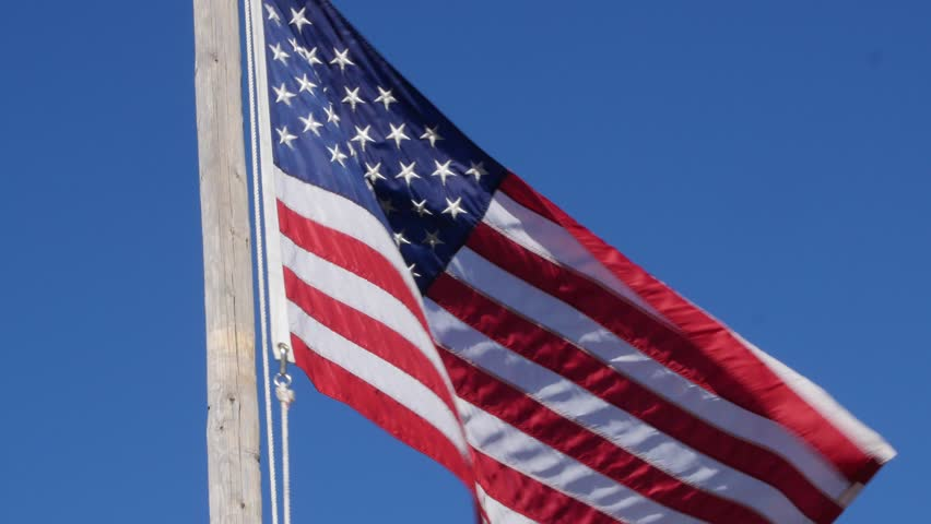 A beautiful American flag blows in a strong wind against a blue sky backdrop - 4K stock video clip