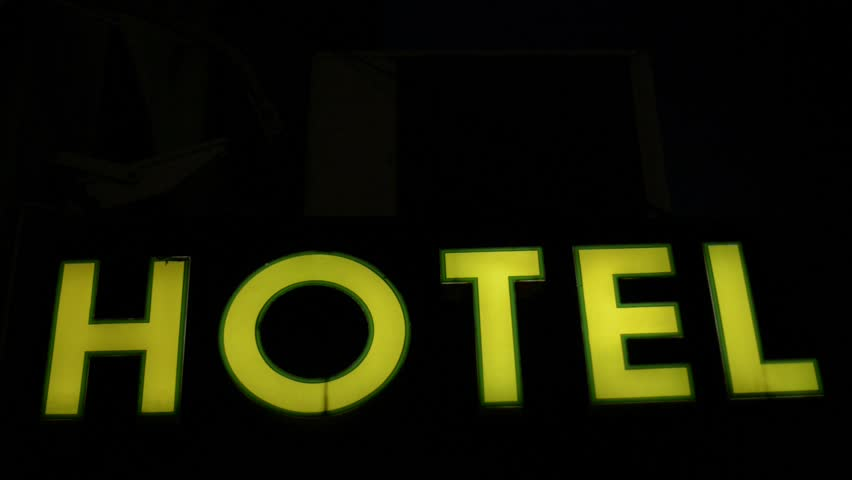 yellow hotel sign in night