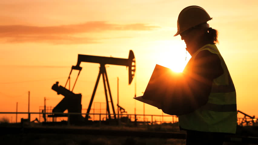 Silhouette of female engineer with clipboard using a cell phone overseeing the site of crude oil production at sunset