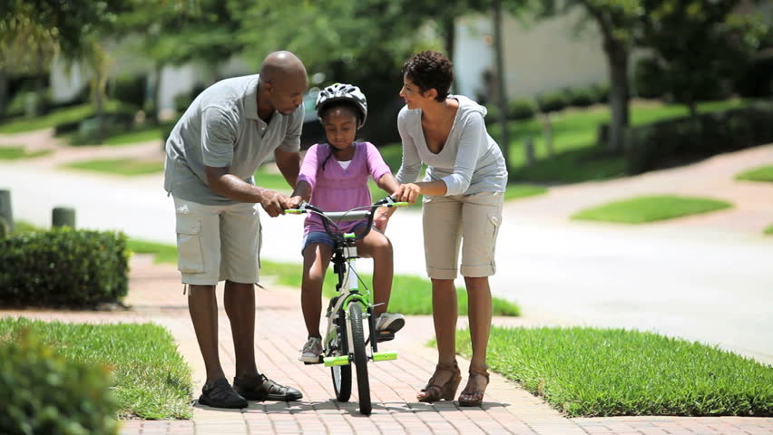 Cute little african american girl being encouraged by her parents as she practices riding her bicycle - HD stock footage clip