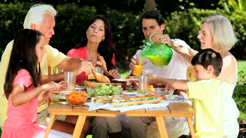 Three generations of caucasian family sitting outdoors sharing a healthy lunch together