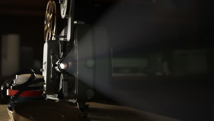 Front view of an old-fashioned antique Super 8mm film projector, projecting a beam of light in a dark room next to a stack of unraveled film reels. Includes projector audio.