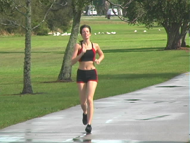 A beautiful young woman jogging outdoors toward the camera (full-length) - SD stock footage clip