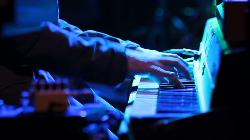 This is a close up shot of a hand playing a keyboard in at a rock n roll concert. - HD stock footage clip