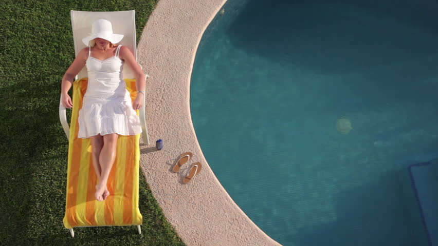 Cinemagraph - Woman laying by pool at tropical resort. Looping Motion Photo.