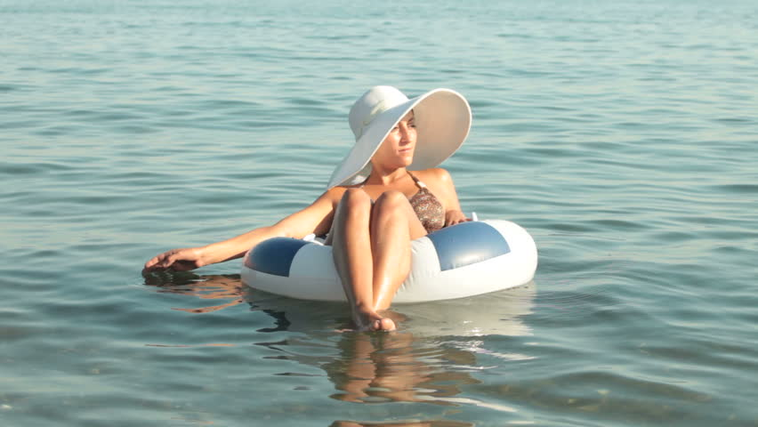 woman in a white hat floating on the  inner tube - HD stock footage clip