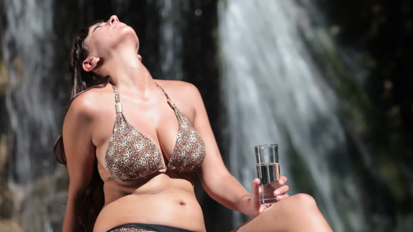 woman in bikini drinking fresh water from a glass while sitting by the waterfall - HD stock video clip