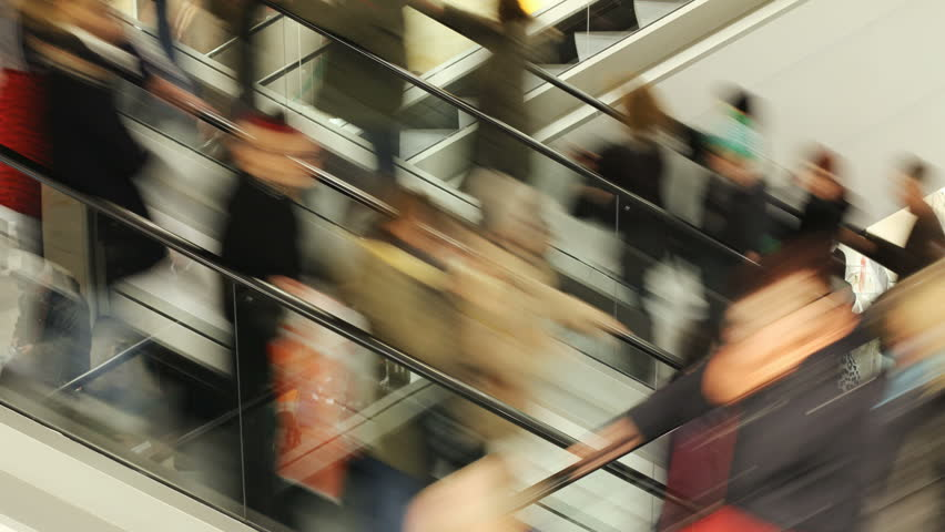 People on fast moving escalator in public building
