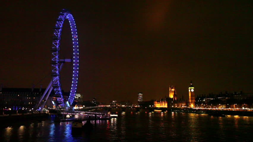 London skyline at night with Big Ben, Houses of Parliament, Westminster Bridge, Millennium Wheel, and Thames River - HD stock video clip
