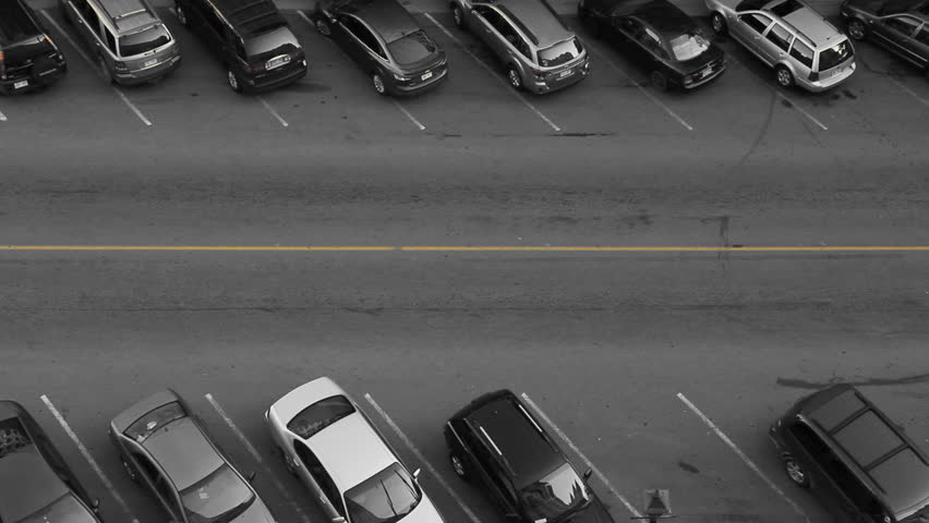 Car finds parking spot. Aerial view of downtown street. Car finds parking spot. Black and white with yellow line. Saint John, New Brunswick, Canada.