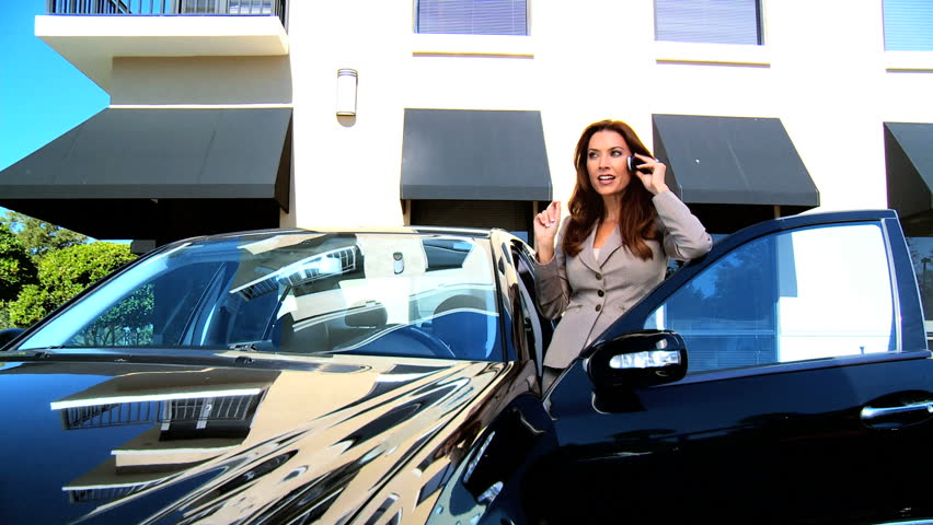 Young female business executive in city clothes using a cell phone before getting into her car - HD stock footage clip