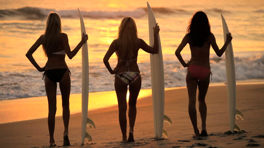 Three young girls with surfboards watching the waves at sunrise - HD stock video clip