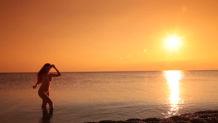 silhouette of young woman in a bikini coming out of the sea at sunset - HD stock footage clip