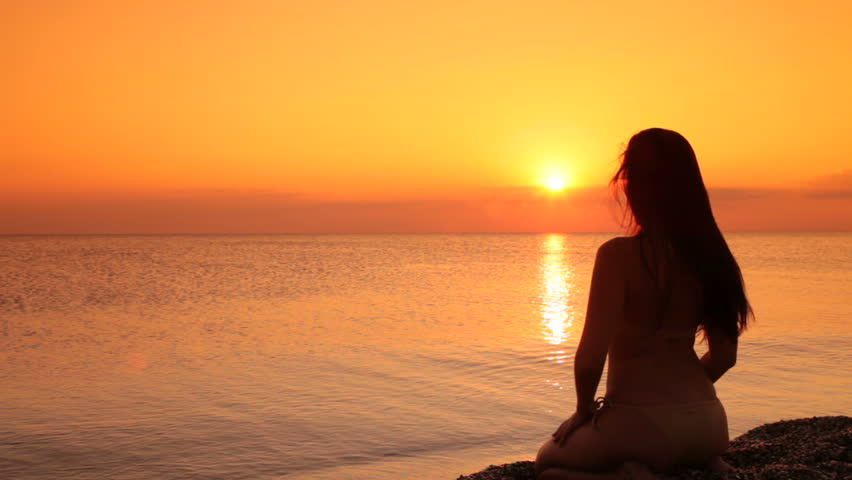 silhouette of a woman sitting on a beach at sunset - HD stock footage clip