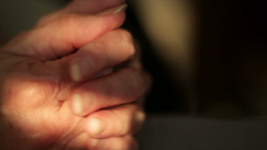 Camera pans left over the hands and fingers of an older woman expressing anxiety or worry. - HD stock video clip