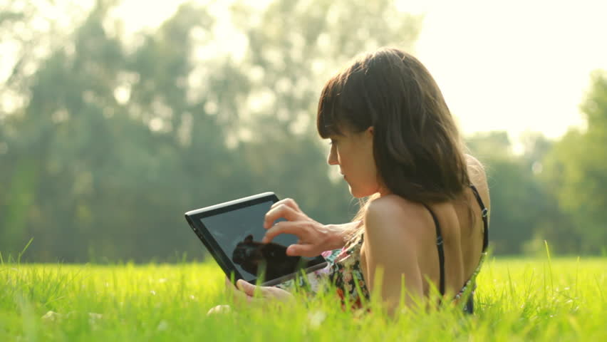 Young woman with tablet computer on meadow - HD stock footage clip