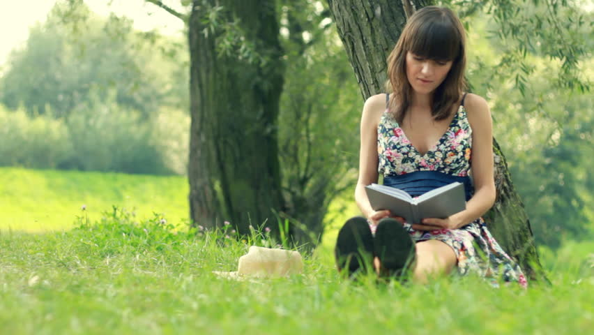 Young attractive woman reading book by the tree in park, dolly shot - HD stock video clip