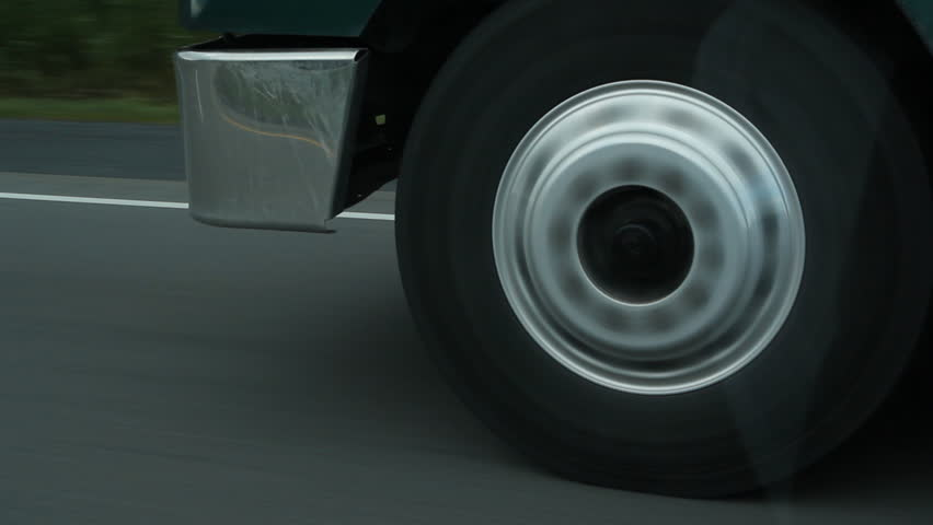 Truck wheel. Closeup of a truck wheel on the highway. Reflection in passenger window.