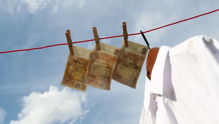 banknotes are waving in the wind on a clothesline beneath a white shirt  - HD stock footage clip