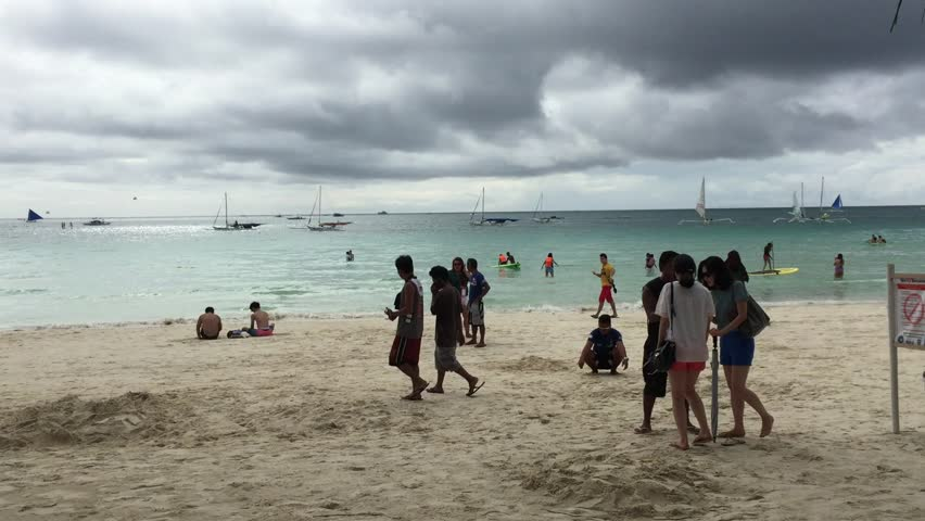 BORACAY, PHILIPPINES - OCT 3, 2014: Tourists walking on the beach in Boracay island, Philippines.
