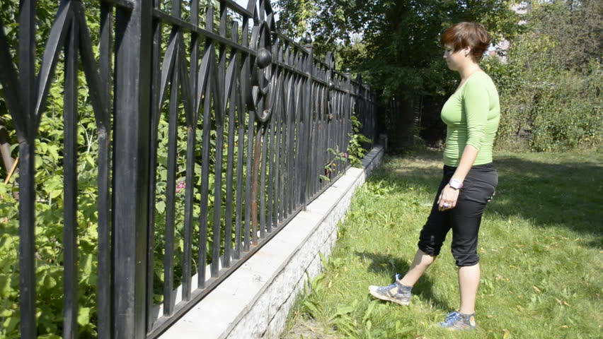 A young woman stretches her legs before jogging - HD stock video clip