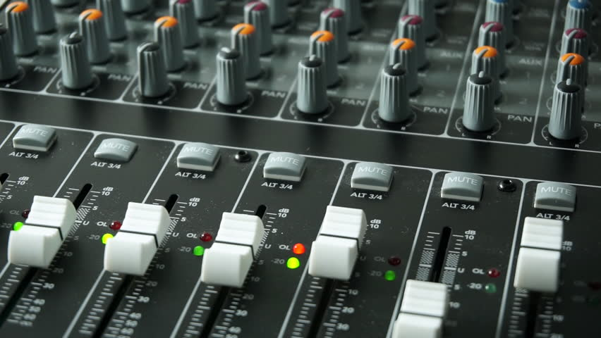 A mixing desk or mixing console being used to mix a track in a recording studio. With level and overload lights, faders and pots / knobs. Engineer's hand adjusting level gain on faders.