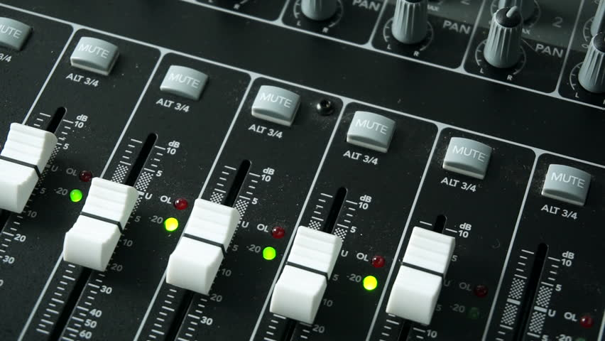 Overhead shot of a mixing desk or mixing console being used to mix a track in a recording studio. With level and overload lights, faders and pots / knobs.