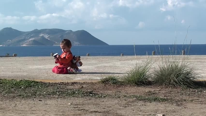 Playing child sitting alone on cement site with sea view in the background