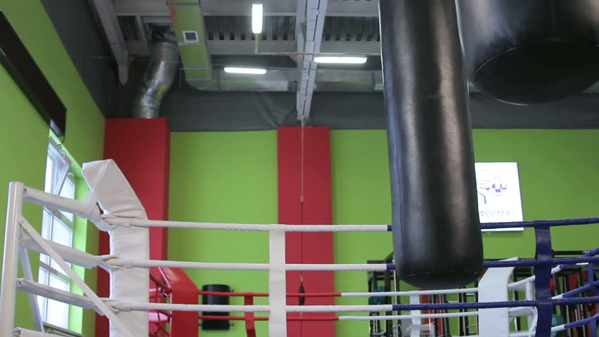 Kickboxing classes. Man fulfills blows by feet on a punching bag