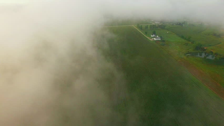 Dense clouds of ground fog engulf rural Wisconsin landscape in autumn, aerial view.