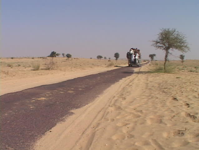 An overcrowded bus drives through the desert on narrow road. - SD stock footage clip