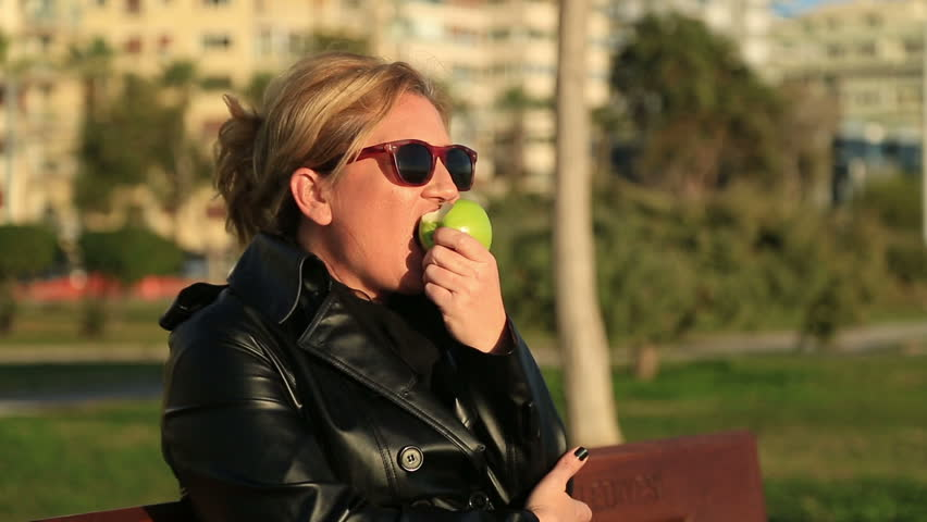 Portrait of a woman sitting on a park bench and eating green apple