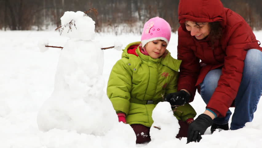 mother with cute little daughter make small snowman - HD stock video clip