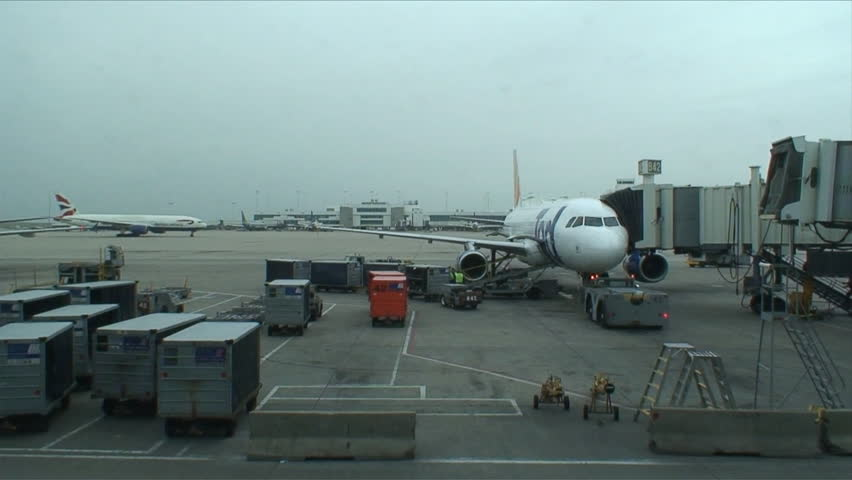 Static shot of plane in boarding area being loaded with luggage - HD stock video clip