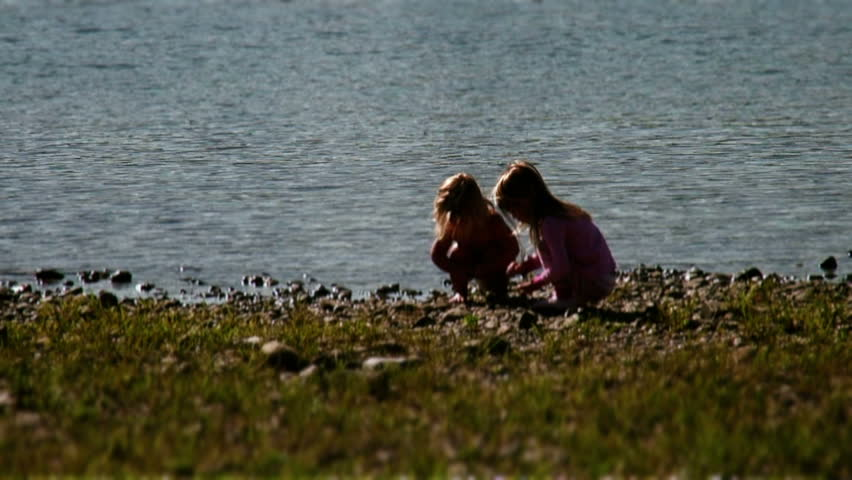 Kids playing at shoreline of river throwing rocks - HD stock video clip