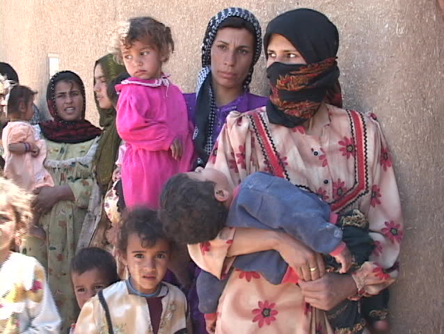 IRAQ - CIRCA 2003: Women and children wait to get into a rural  medical clinic circa 2003 in Iraq.