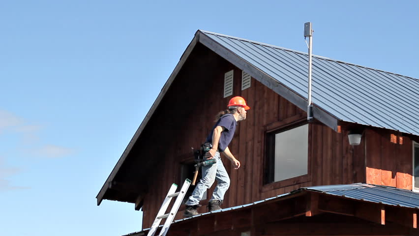 Maintenance Worker On A Roof Installing A Cellular Phone
