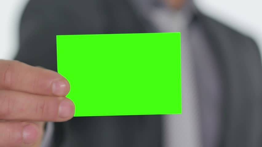 male hand handing a green business card to the camera pre keyed
