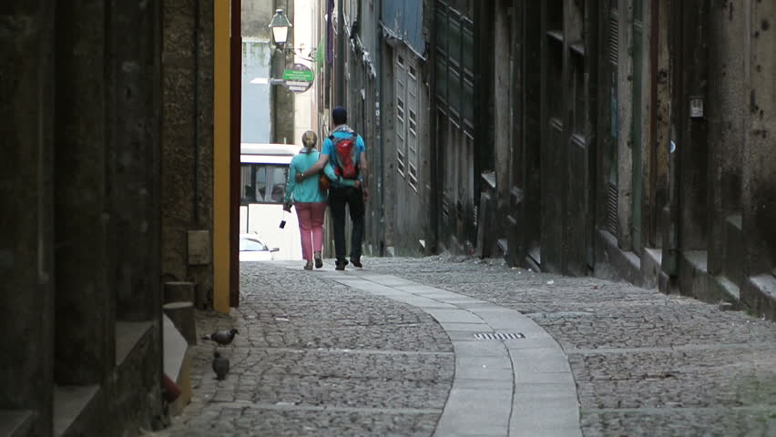 Full length of a young couple in love walking in old town and discovering the city - seen from behind - unrecognizable persons