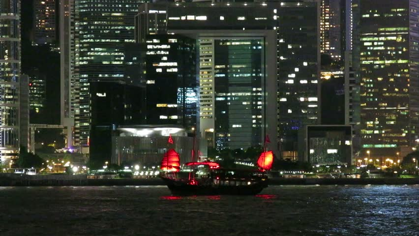 Skyscrapers and light display at night in Victoria Harbour of Hong Kong. Junk boat is in the harbour.