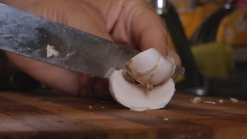 Slicing of mushrooms on a chopping board