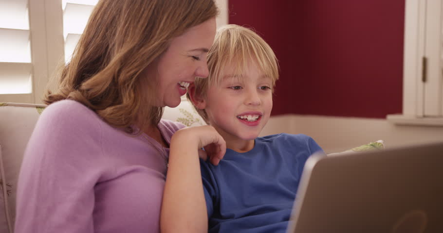 Handsome young boy looking at a laptop computer screen with mom - 4K stock footage clip