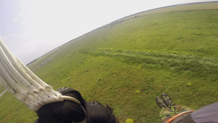 Parachutist in camouflage suit hitting hard the ground. View from the camera on helmet. - HD stock video clip